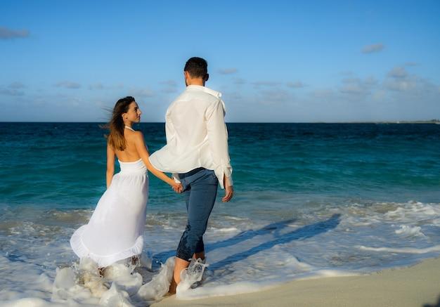 Liebevolles paar, das im sommer am sandstrand gegen kristallblaues wasser am sand tanzt