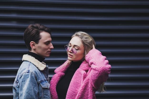Liebevolles paar, das im stadthintergrund aufwirft