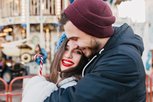 Liebevolles paar, das im winterwochenende im vergnügungspark umarmt. glückliches schwarzhaariges mädchen, das weihnachten mit freund feiert und vor karussell am kalten tag aufwirft.