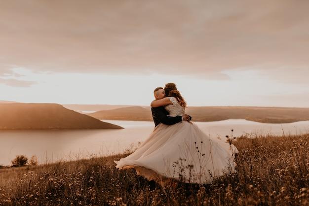 Liebevolles paar, das jungvermählten im weißen kleid und in der anzugumarmung küsst, wirbelt wirbel auf hohem gras im sommerfeld auf berg über dem fluss