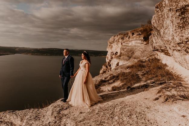 Liebevolles paar, das jungvermählten in einem weißen kleid und anzug heiratet, spazieren im sommer auf dem berg über dem fluss