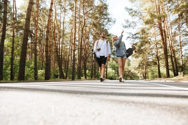 Liebevolles paar, das mit skateboards draußen geht.