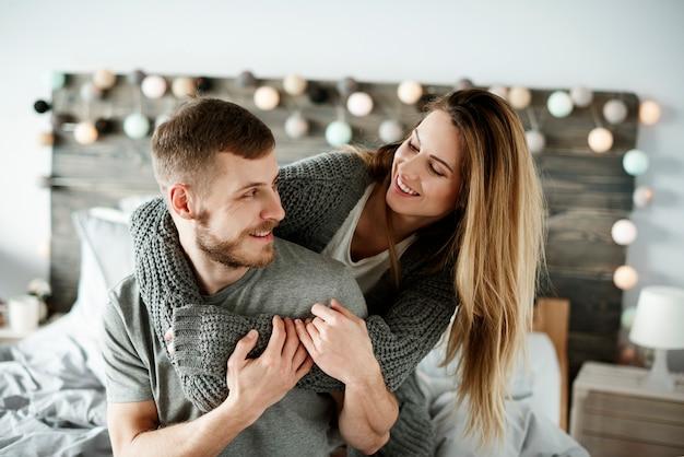 Liebevolles paar, das sich im schlafzimmer amüsiert