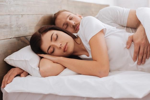 Liebevolles paar, das sich umarmt, während es sich ausruht und zusammen im bett schläft