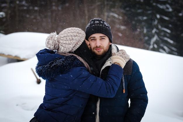 Liebevolles paar in winterkleidung küssen, während eines schneefalls auf einem kiefernwald