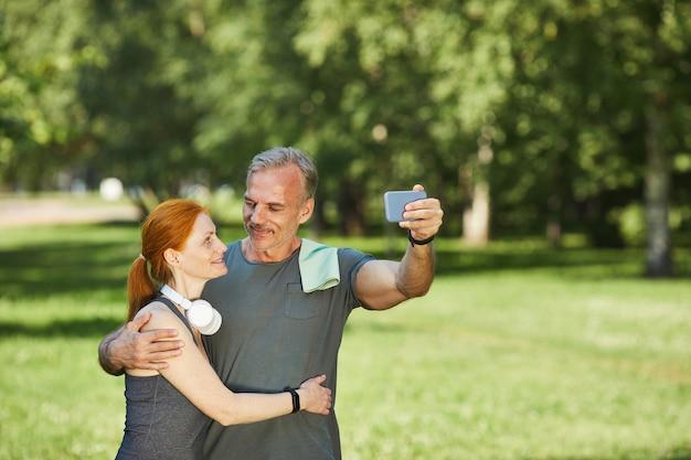 Liebevolles reifes paar, das sich gegenseitig ansieht und umarmt, während für selfie im park nach sporttraining posiert