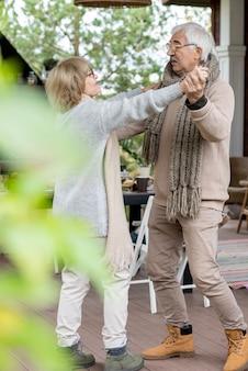 Liebevolles seniorenpaar in warmer, stilvoller freizeitkleidung, das auf dem holzboden der terrasse neben ihrem landhaus gegen den gedeckten tisch tanzt