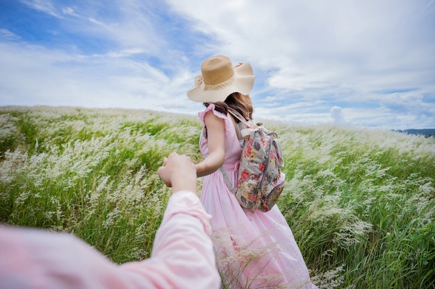 Liebhaber, die hände halten, kommen, um auf der wiese zu reisen.