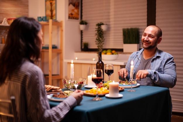 Liebhaber, die leckeres essen beim abendessen in der küche genießen. entspannen sie sich glückliche menschen, sitzen sie am tisch in der küche, genießen sie das essen, feiern sie jubiläum im esszimmer.