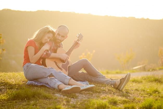 Liebhaber in der natur. junges verliebtes paar, das auf dem park sitzt, während diese junge gitarre gitarre in der sonnenuntergangszeit spielt.