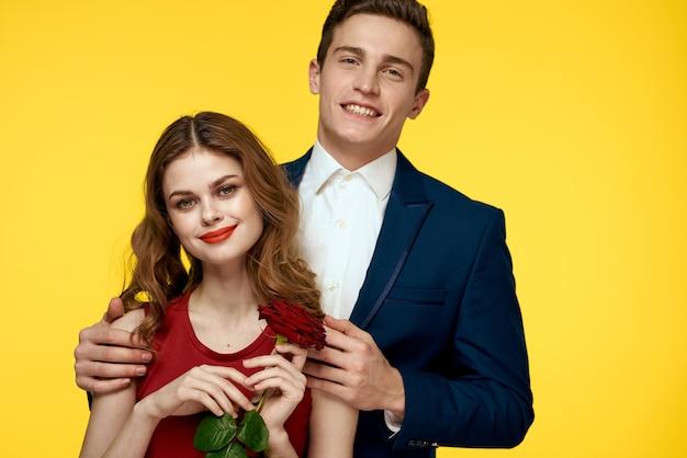 Liebhaber mann und frau mit einer roten rose in den händen umarmen sich auf einem gelben