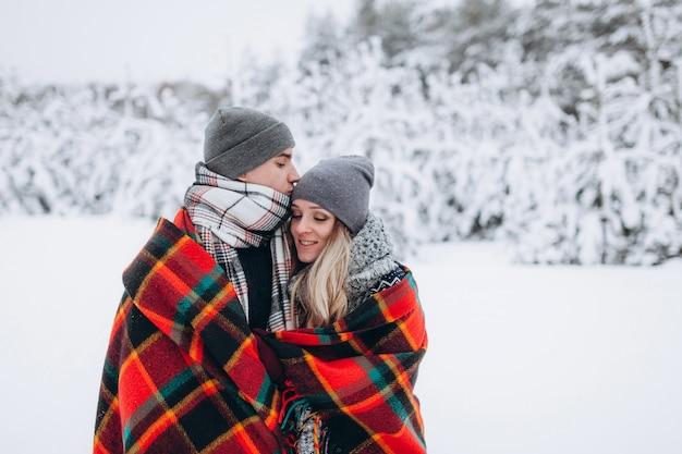 Liebhaber stehen bedeckt mit einer decke vor dem hintergrund eines schneebedeckten winterwaldes