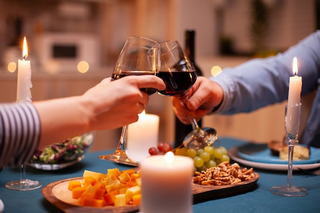 Liebhaber stoßen weingläser im speisesaal zum beziehungsjubiläum an. fröhliches, fröhliches junges paar, das in der gemütlichen küche zusammen isst, das essen genießt und den romantischen toast zum jubiläum feiert