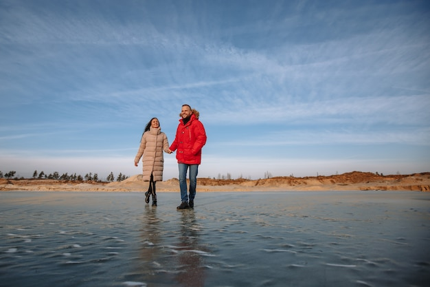 Liebhaber von daunenjacken laufen auf dem eis von sandgruben