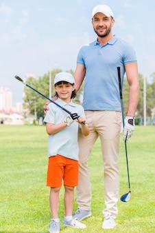 Lieblings-familienspiel. fröhlicher junger mann, der seinen sohn umarmt, während er auf dem golfplatz steht