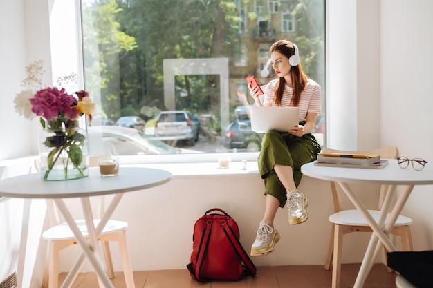 Lieblings-playlist. ernsthafte frau, die laptop auf den knien hält, während sie auf der fensterbank sitzt