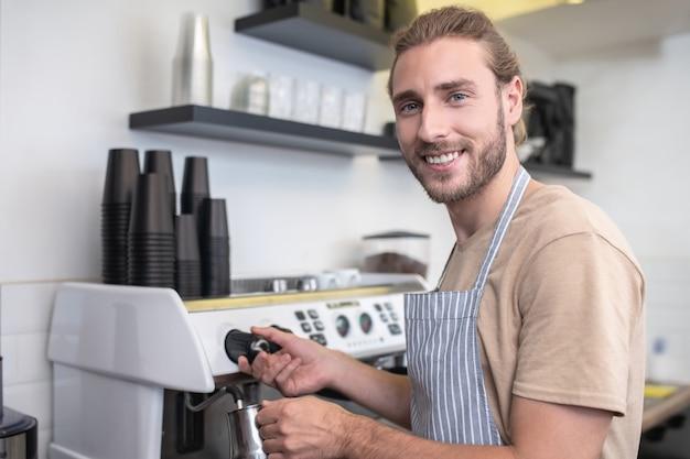 Lieblingsarbeit. beschäftigter glücklicher junger bärtiger mann, der wasser für kaffee gießt, während in seinem café