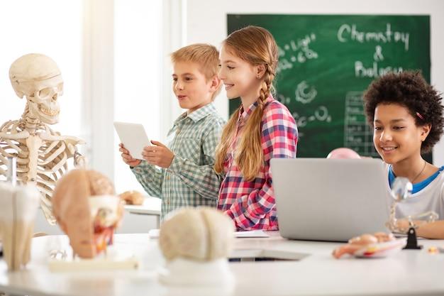 Lieblingsfach. glücklich entzückte kinder, die das skelett betrachten, während sie ihren biologieunterricht genießen