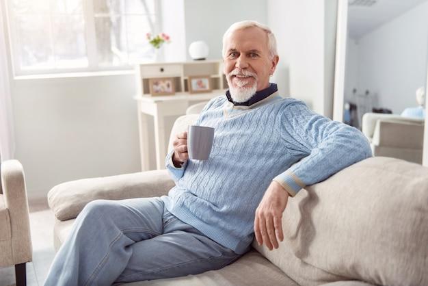 Lieblingsgetränk. optimistischer älterer bärtiger mann, der bequem auf der couch sitzt und posiert, während er eine tasse kaffee hält