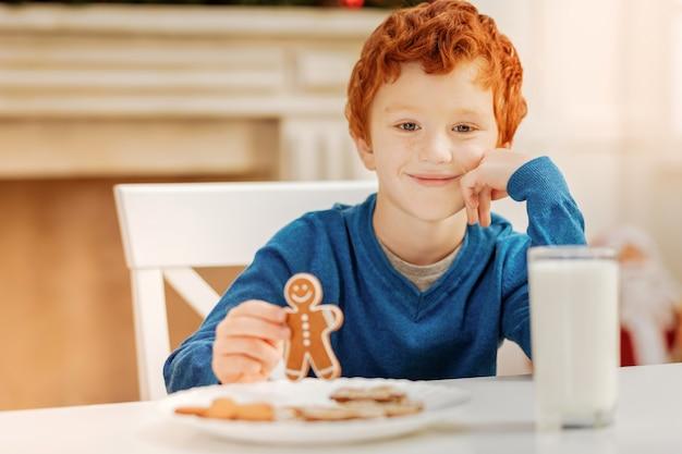 Lieblingsjahreszeit. charmanter kleiner junge, der seinen kopf auf einer hand ruht, während er einen lebkuchenmann hält und lächelt
