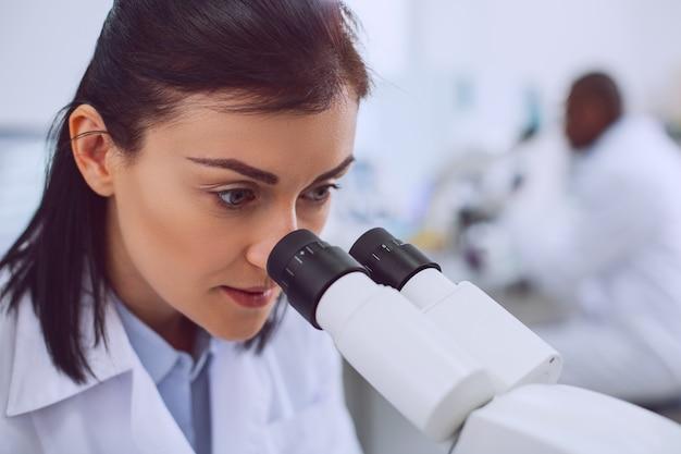Lieblingsjob. ernsthafte kluge wissenschaftlerin, die mit ihrem mikroskop arbeitet und eine uniform trägt