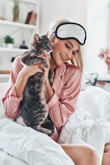 Lieblingskatze. attraktive junge frau, die mit ihrer katze spielt und lächelt, während sie zu hause im bett sitzt