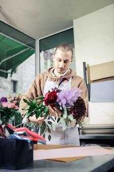 Lieblingskunst. hübsche männliche person, die positivität beim betrachten von pflanzen ausdrückt