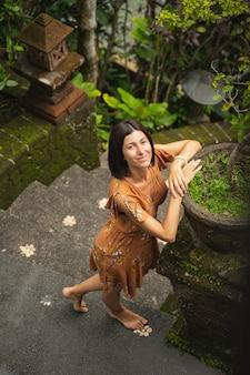 Lieblingsort. erfreute brünette weibliche person, die beim stehen auf der treppe ein lächeln auf ihrem gesicht hält
