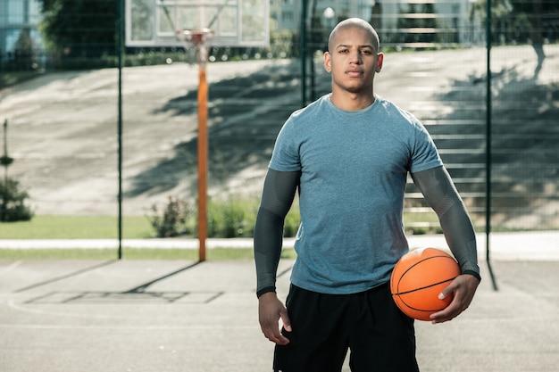 Lieblingsspiel. ernsthafter afroamerikanischer mann, der sie beim stehen mit einem basketballball betrachtet