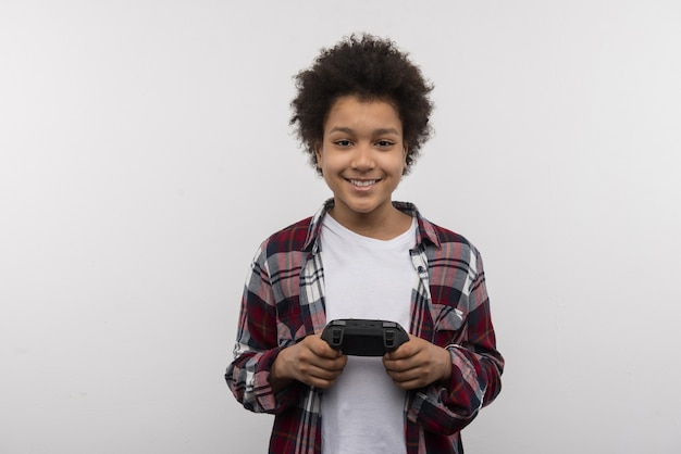 Lieblingsspiel. fröhlicher netter junge, der sie beim spielen von videospielen ansieht