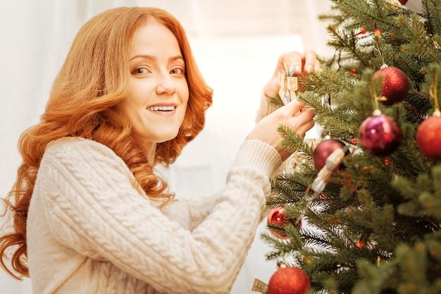 Lieblingszeit des jahres. niedriger winkelschuss einer himmlischen schönheit, die lächelt, während sie einen weihnachtsbaum verziert.