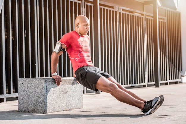 Liebste aktivität. angenehmer junger mann, der sein training genießt, während er einen gesunden lebensstil pachtet