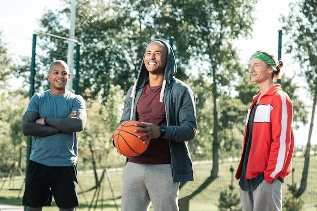 Liebste aktivität. freudiger afroamerikanischer mann, der seine positiven gefühle zeigt, während er genießt, basketball zu spielen
