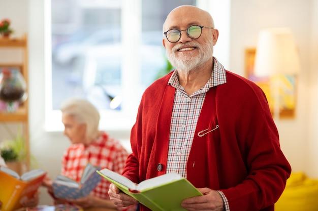 Liebste aktivität. fröhlicher alter mann, der mit einem buch steht, während er es genießt, es zu lesen