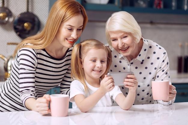 Liebste leute. schönes kleines mädchen, das an der küchentheke sitzt und ein selfie mit ihrer geliebten mutter und großmutter nimmt, während die frauen tassen kaffee halten