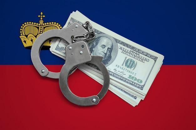 Liechtenstein flagge mit handschellen und einem bündel von dollar. währungskorruption im land. finanzielle verbrechen