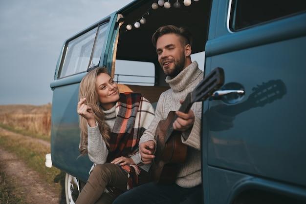 Lied für sie. hübscher junger mann, der gitarre für seine schöne freundin spielt, während er im blauen retro-stil-minivan sitzt