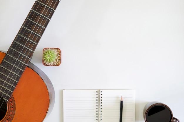 Liederschreibertabelle ein arbeitsplatz mit musikerakustikgitarre und kaffeetasse mit notizblockpapier auf draufsichtschreibtisch.