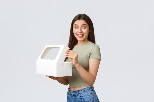 Liefer-, lifestyle- und food-konzept. lächelnde glückliche freundin offene weiße kiste mit süßen köstlichen desserts, kuchen oder muffins, die in der besten konditorei bestellt wurden, stehender weißer hintergrund.