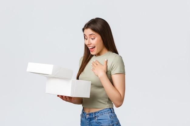 Liefer-, lifestyle- und food-konzept. überraschte glückliche frau erhält eine überraschungsgeschenkbox mit desserts, köstlichen süßen kuchen und muffins, die nach innen staunen und auf weißem hintergrund stehen.
