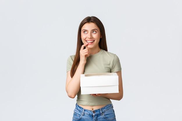 Liefer-, lifestyle- und food-konzept. verträumte, glückliche, stilvolle frau, die nachdenklich aufschaut, lächelt, als sie sich etwas vorstellt, eine schachtel mit desserts hält, köstliche speisen bestellen, weißer hintergrund steht.