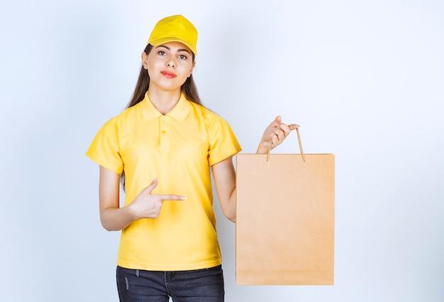 Lieferangestelltfrau in der gelben kappe, die braunes kraftpapier auf weiß hält.