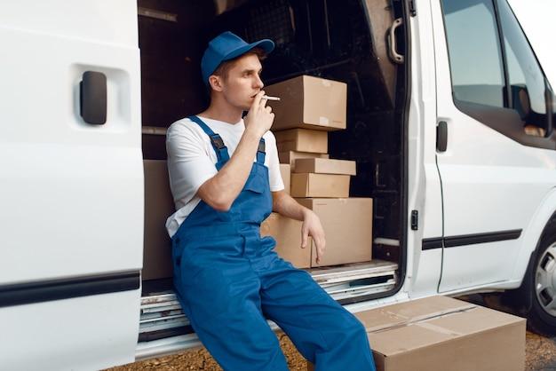 Lieferant in uniform raucht während einer pause am auto, auto mit paketen und kartons, lieferservice. mann, der an den papppaketen im fahrzeug, im männlichen liefer-, kurier- oder versandjob steht