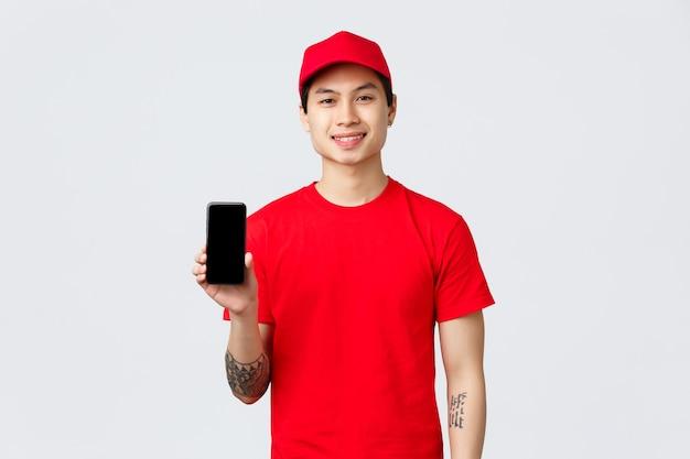 Lieferanwendung, online-shopping und versandkonzept. lächelnder lieferbote in roter uniform, mütze und t-shirt, der den handy-bildschirm zeigt, ratschläge zum herunterladen der app für den bonus zur bestellung.