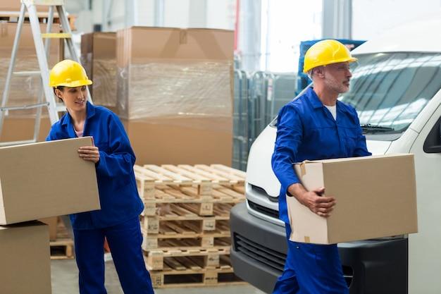 Lieferarbeiter entladen pappkartons vom palettenheber