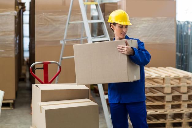 Lieferarbeiter entlädt pappkartons vom palettenheber