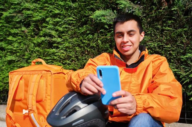 Lieferbote auf einem fahrrad, der mit seinem smartphone auf eine bestellung wartet, die an eine privatadresse geliefert wird
