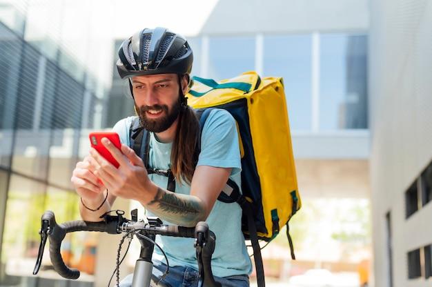 Lieferbote auf fahrrad mit blick auf smartphone