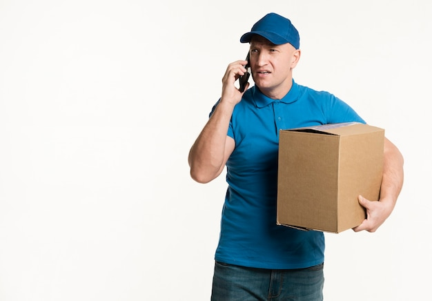 Lieferbote, der am telefon beim tragen der pappschachtel spricht