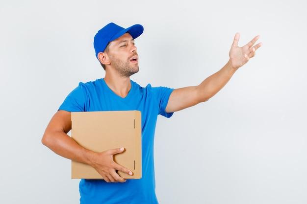 Lieferbote, der an jemanden mit pappkarton im blauen t-shirt adressiert